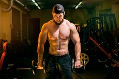 Человек в тренировке спортзала с гантелями Стоковые Фото
