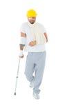 Человек в трудной шляпе с сломленными рукой и костылем стоковое фото rf