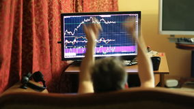 Человек в футболке и шортах, сидя дома на кресле, мониторы изменяет в план-графике на валютной бирже видеоматериал