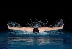 Человек в черной крышке в бассейне Стиль бабочки Стоковая Фотография
