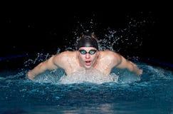 Человек в черной крышке в бассейне Стиль бабочки Стоковые Изображения