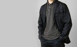 Человек в черной куртке Руки в его карманн Изолировано на сером цвете стоковые изображения