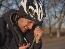 Человек в шлеме прячет телефон Стоковые Изображения RF