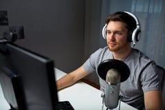 Человек в шлемофоне играя видеоигру компьютера дома Стоковое Изображение