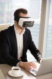 Человек в шлемофоне VR печатая на компьтер-книжке на рабочем месте Стоковая Фотография RF