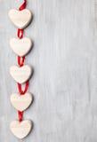 человек влюбленности поцелуя принципиальной схемы к женщине Сердца вися на серой предпосылке Стоковые Фотографии RF