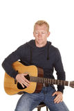Человек в hoodie с взглядом гитары вниз Стоковые Фото