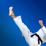 Человек в karategi бьет прямой пинок Стоковые Фото