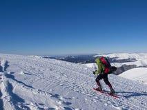 Человек в snowshoes в горах Стоковая Фотография