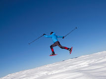 Человек в snowshoes скачет в горы Стоковое Изображение RF