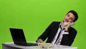 Человек говорит для личных дел на телефоне к рабочему месту сток-видео