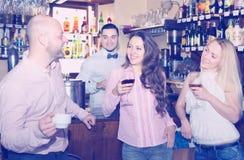 Человек говоря к женщинам в баре Стоковая Фотография RF