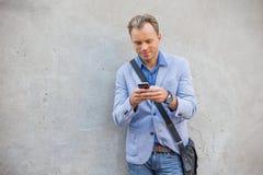 Человек готовя стену и используя smartphone Стоковые Фотографии RF