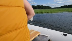Человек гребя раздувную шлюпку с деревянными веслами на озере Задний отснятый видеоматериал образа жизни взгляда HD Slowmotion видеоматериал