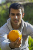 Человек держа апельсин Стоковые Изображения RF