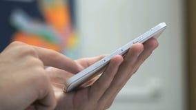 Человек держа белый мобильный телефон внутри помещения видеоматериал