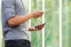 Человек держа внешнюю батарею и умный телефон стоковое изображение rf