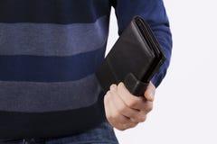 Человек держа закрытый бумажник Стоковая Фотография