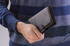 Человек держа закрытый бумажник Стоковое фото RF