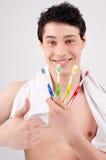 Человек держа зубные щетки различных цветов. Стоковые Изображения