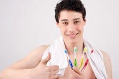 Человек держа зубные щетки различных цветов. Стоковая Фотография RF