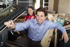 Человек держа ключ автомобиля с женщиной около его в автомобиле с откидным верхом Стоковая Фотография RF