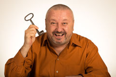 Человек держа ключ к успеху смотря изумленный Стоковая Фотография
