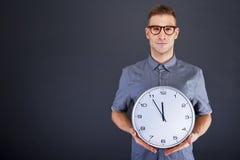 Человек держа настенные часы стоковые фото
