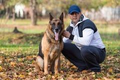 Человек держа немецкую овчарку собаки Стоковые Фото