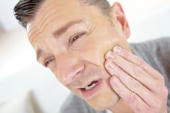 Человек держа опухнутую челюсть выражая acke зуба Стоковое Изображение