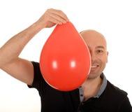 Человек держа оранжевый воздушный шар  Стоковая Фотография RF