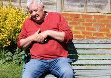 Человек держа пальцы и руку Тягостный артрит стоковое фото rf