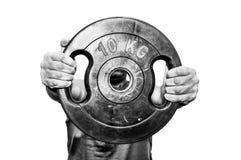 Человек держа плиту веса изолированный на белой предпосылке черная белизна Стоковая Фотография