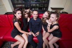 Человек держа сотовый телефон затем 4 девушки Стоковая Фотография