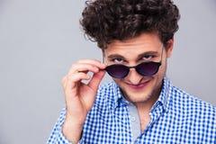Человек держа солнечные очки и смотря камеру стоковое фото rf