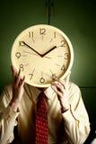Человек держа часы к его стороне стоковые изображения