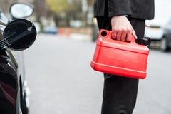 Человек держа чонсервную банку топлива, подрезанное изображение Стоковое фото RF