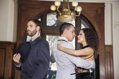 Человек держа шляпу пока мужской и женские танцоры выполняя танго Стоковая Фотография