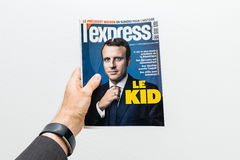 Человек держа l срочную газету Le ребенк с Emmanuel Macron на f Стоковое фото RF