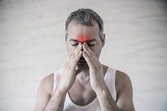 Человек держит его зону носа и синуса с пальцами в очевидной pabvious боли от головной боли в передней зоне лба Стоковая Фотография RF