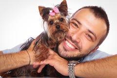 Человек держит его собаку щенка йоркширского терьера любимчика стоковое изображение