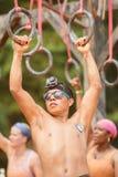 Человек держит на приостанавливанные кольца на весьма гонке полосы препятствий Стоковые Фото