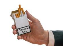 Человек держит пакет сигареты в руке с убийствами предупреждающего ярлыка куря Стоковое Фото