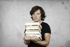 Человек держит руки много книг стоковое изображение rf