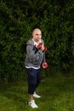 Человек держит для того чтобы приспосабливать с разминками гантели outdoors Стоковое фото RF