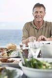 Человек есть еду около моря Стоковые Фотографии RF