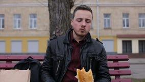 Человек ест горячую сосиску в городе на стенде сток-видео