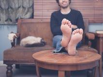 Человек детенышей босоногий отдыхая на софе дома стоковые фотографии rf