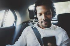 Человек детенышей усмехаясь африканский используя smartphone пока сидящ на заднем сиденье в автомобиле такси Концепция бизнесмено Стоковое фото RF