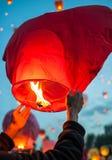 Человек делает желание и запускает красный бумажный фонарик стоковая фотография